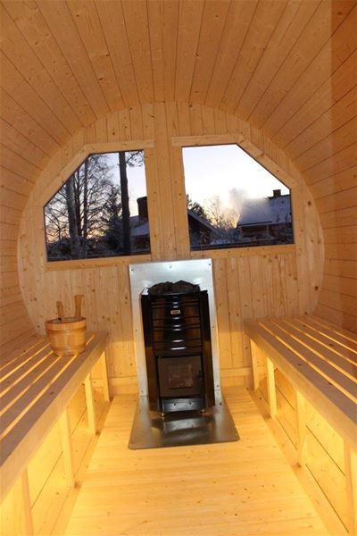 Interiörbild av bastutunna. Bastulavar, kamin och stora fönster.