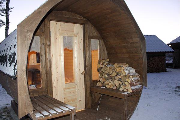 Exteriörbild på bastutunna utvändigt med bänkar och ved utanför ytterdörren.