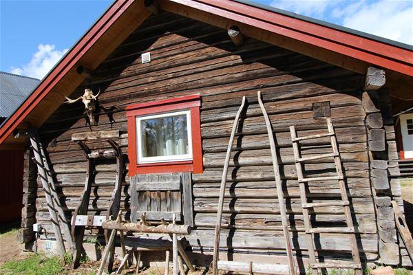 Timmerstugevägg med gamla redskap som stege i trä, släde, sågbock.