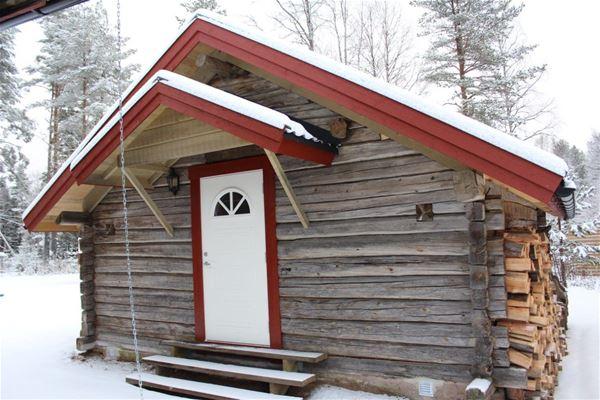 Grå timmerstuga med röda foder och vit dörr.