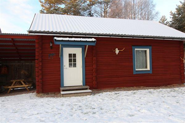 Faluröd timmerstuga med blå foder och vit dörr. Snö på tak och gräs.