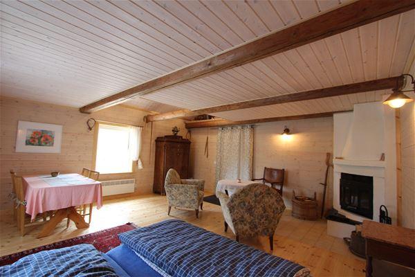 Interiörbild av stuga med 2 fåtöljer, öppen spis och matbord.