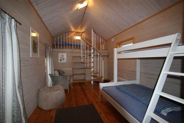 Vitmålad våningssäng, fåtöljer, spiraltrappa till loft.