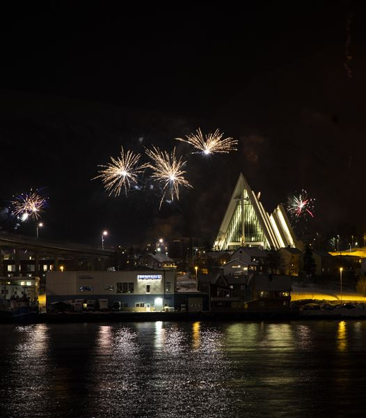© Ishavskatedralen, The Arctic Cathedral seen from Tromsø city centre, fireworks in the background