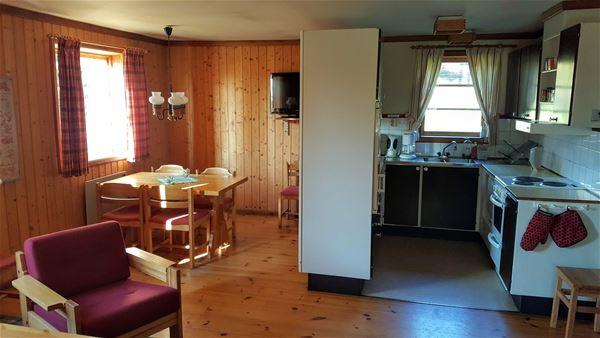 allrum med röd fåtölj och köksavdelning med spis samt fönster.