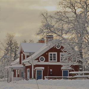 Rödmålat hus i vinterlandskap.