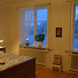Sovrum med två fönster och en dubbelsäng.