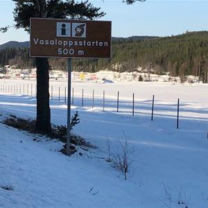 Vinterbild från ett öppet fält. Skylt med Vasaloppets start 500 m.