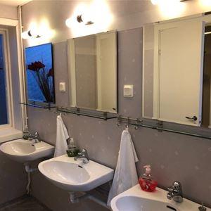 Sanitetsrum med tre tvättställ och speglar.