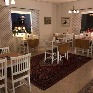 Matsal med flera bord och stolar.