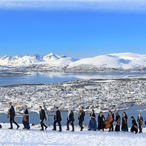 Rune Stoltz Bertinussen,  © Arktisk Filharmoni, A parade of musicians carrying their instruments on top of the mountain Fløya, view over Tromsø island