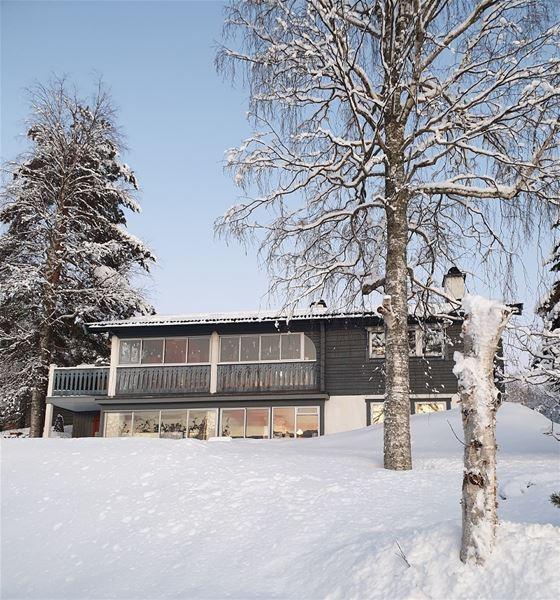 Baksidan av huset, med trädgård täck i snö.