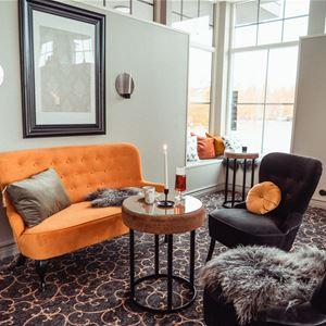 Lounge med modern sittgrupp och mönstrad heltäckningsmatta.
