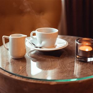 Litet runt bord med en kaffekopp och en ljuslykta.