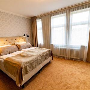 Dubbelrum med gyllenbruna färger på heltäckningsmatta, gardiner och sänggavel.