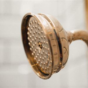 Detalj av mässingsfärgat duschmunstycke.