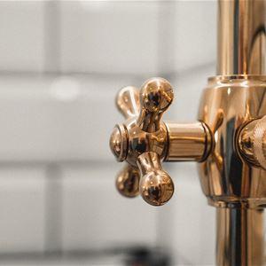 Detalj av mässingsfärgad duschblandare.