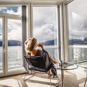 © Malangen Resort, Kvinne nyter kaffe med utsikt over fjorden
