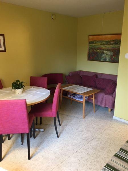 Sitthörna med soffa, soffbord och ett runt bord med fyra stolar.