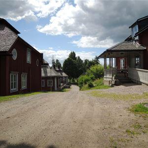 Röda byggnader på vardera sida om en grusväg.