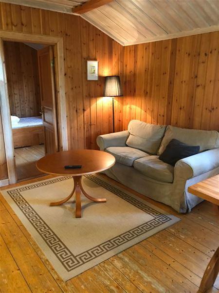 Beige soffa med runt bord i ett rum med väggar, golv och tak av furu.