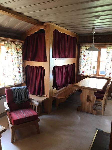 Platsbyggd våningssäng med röda draperier, ett matbord och en röd fåtölj.