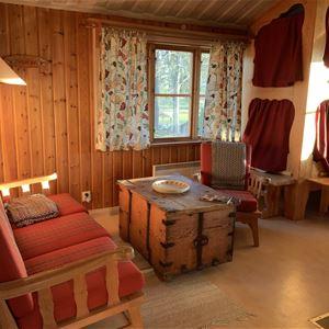 Platsbyggd våningssäng med röda draperier och en röd soffa med kista som soffbord.