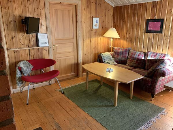 Röd-rutig soffa, röd fåtölj och soffbord i ett rum med väggar, tak och golv av furu.