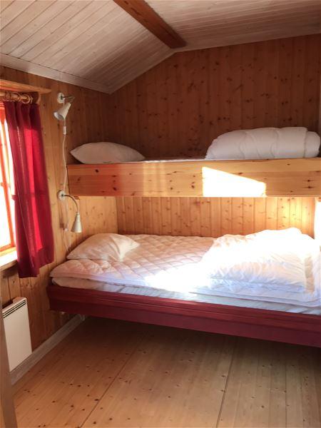 Familjesäng i ett rum med väggar och golv av furu.
