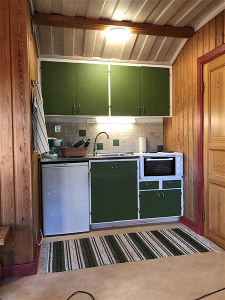 Pentry med gröna skåpluckor och en grön-randig trasmatta.