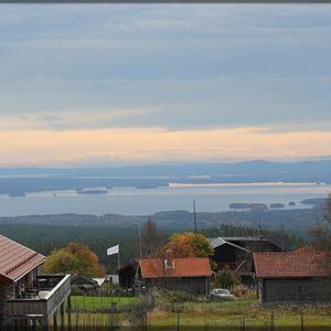 Vy över Fryksås med gråa fäbodstugor i förgrunden och Orsasjön i bakgrunden.