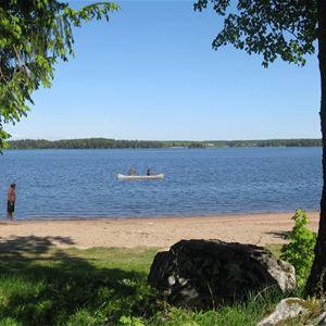 Vy över sandstranden och sjön, med en kanot ute på sjön.