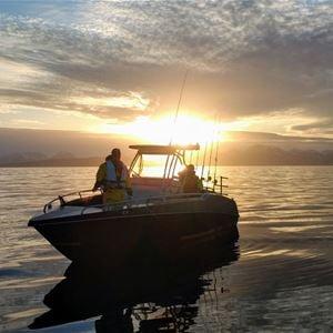 © Jæger Adventure Camp, Båt på havet, midnattsol i bakgrunnen