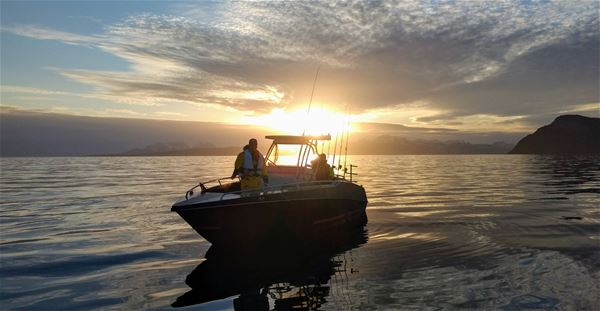© Jæger Adventure Camp, Boat on the sea, midnight sun in the background