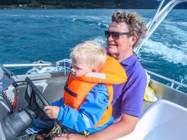 © Dyrøy Holiday, Mann og barn kjører båt