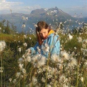 © Dyrøy Holiday, Girl sitting on the ground surrounded by cotton grass