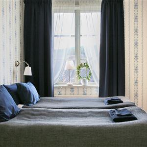 Dubbelsäng i smalare rum med fönster ut mot Stora Stöten vid Falu Gruva.