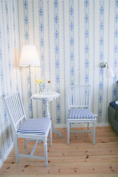Två stilfulla stolar vid ett bord i ett av rummen med ljusa gammeldags tapeter i nyskick.