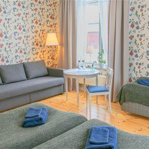Tre sängar och en soffa i ett större trippelrum med ljusa färger.