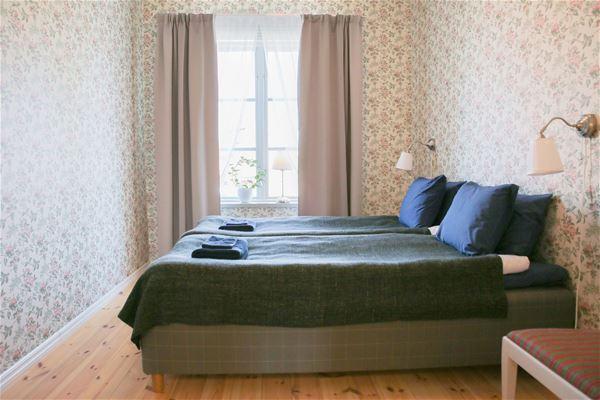 Dubbelsäng i smalt rum med fönster i kortsidan med utsikt ut över Stora Stöten Falu Gruva.