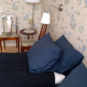 interiörbild med kuddar i dubbelsängen och två stolar med bord i hörnet.