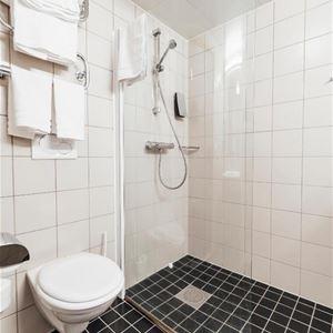 Badrum med dusch med glasdörrar.
