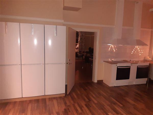 Stort kök med flera kylskåp och frysar.