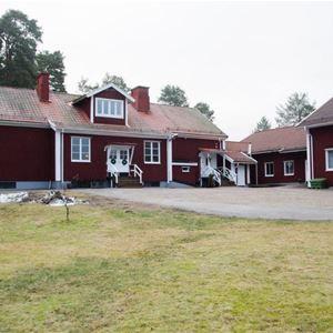Röda byggnader på gården där boende och gymanläggningen finns.