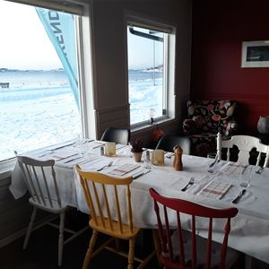 © Skagi Senja hotel & lodge, From inside of the restaurant - a set table