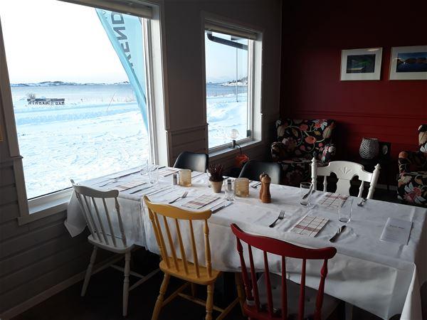© Skagi Senja hotel & lodge, From inside of the restaurant - a set table