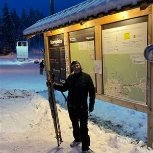 En skidåkare håller i sina skidor framför en stor informationstalvla.