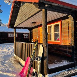 Pulka, längdskidor och snowboard lutar mot altanen på en stuga.