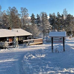 Timmerstuga med snö på taket.