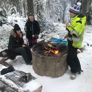 Några personer grillar vid en grillplats en vinterdag.